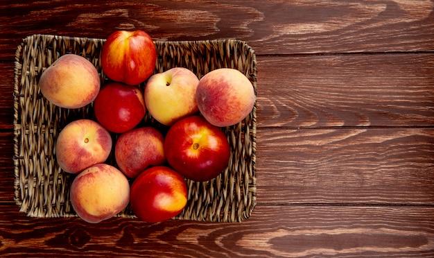 Взгляд сверху свежих зрелых нектаринов и персиков на плетеном подносе на деревянной деревенской таблице с космосом экземпляра