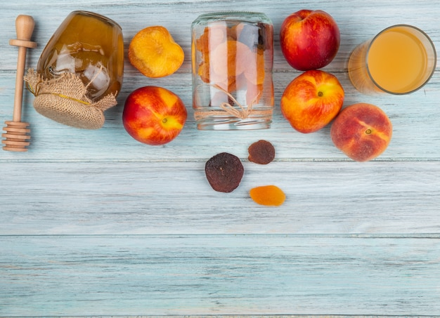 Вид сверху свежих спелых нектаринов с курагой, разбросанных от стеклянной банки меда в банке и стакан персикового сока на деревенском фоне с копией пространства