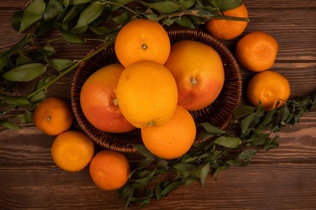 Вид сверху свежих спелых апельсинов в плетеной корзине и зеленые листья на темном дереве