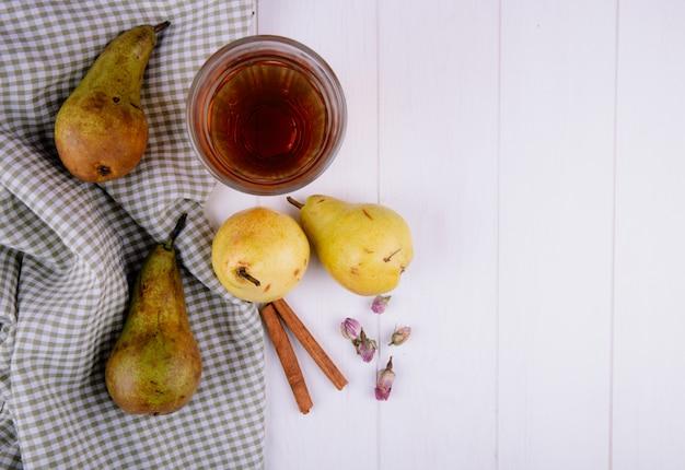白い背景の格子縞のテーブルクロスに新鮮な熟した梨とシナモンスティックジュースのガラスのトップビュー
