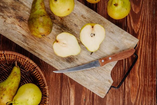 Вид сверху свежих спелых груш и половинок на деревянной разделочной доске с кухонным ножом на деревенском фоне