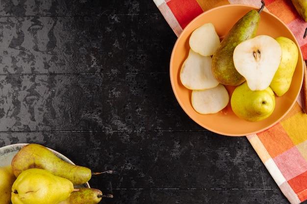 Вид сверху свежих спелых груш и ломтики груш на тарелку на черном фоне с копией пространства