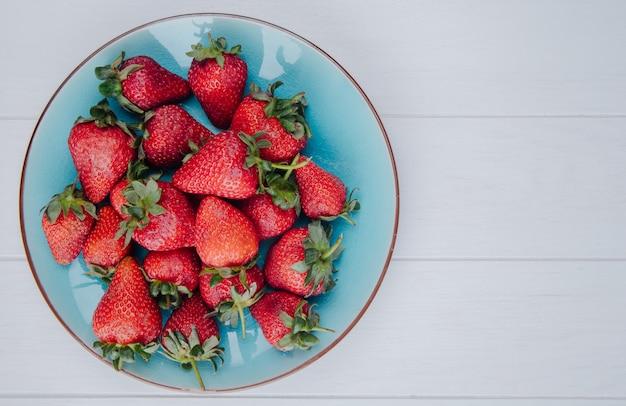 Вид сверху свежей спелой клубники на синюю тарелку на белом с копией пространства