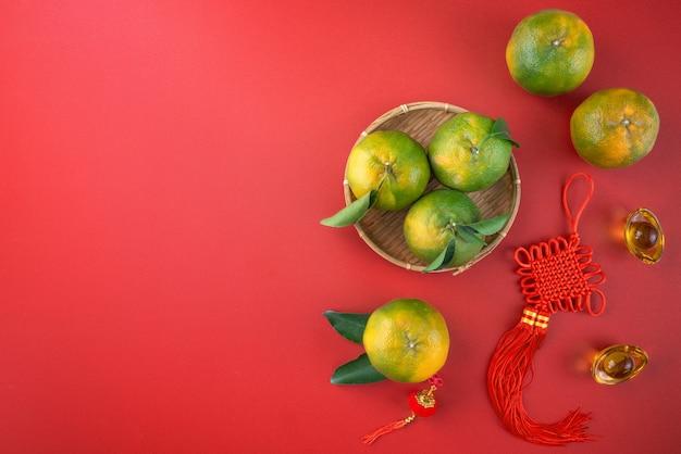 中国の旧正月の果物の概念のための赤いテーブルの背景に新鮮な葉を持つ新鮮な熟したみかんマンダリンオレンジの上面図、中国語の単語は春を意味します。