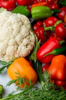 白い背景の上の新鮮な熟した野菜カリフラワートマトカラフルなピーマンと青唐辛子のトップビュー