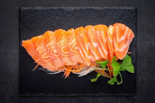 Вид сверху свежего филе сашими из лосося с морковью, ломтиком редиса и сельдереем в черном сланце на темно-сером фоне текстуры