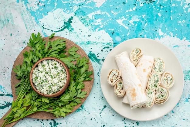 茶色のボウルの中に緑があり、明るい青色の机の上に野菜のロールが付いている新鮮なスライスしたキャベツのサラダの上面図、フードサラダフレッシュスナック