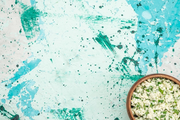 Вид сверху салата из свежей нарезанной капусты с зеленью в коричневой миске на ярко-синей, зеленой закуске из овощного салата