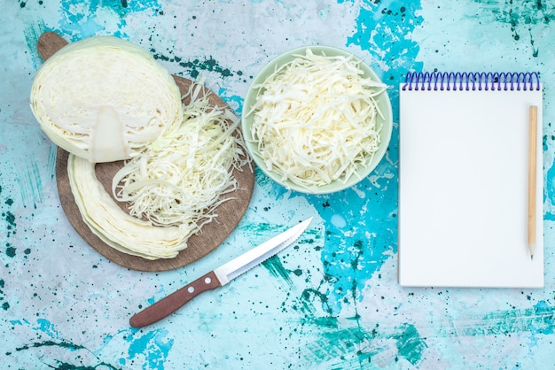 Вид сверху свежей нарезанной капусты с половиной целого овоща и блокнотом на ярко-синем столе, овощная еда, закуска, здоровый салат