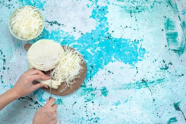 新鮮なスライスしたキャベツの上面図で、野菜の半分が明るい青色の机の上でカットされています。野菜料理、食事、スナック、ヘルシーサラダ