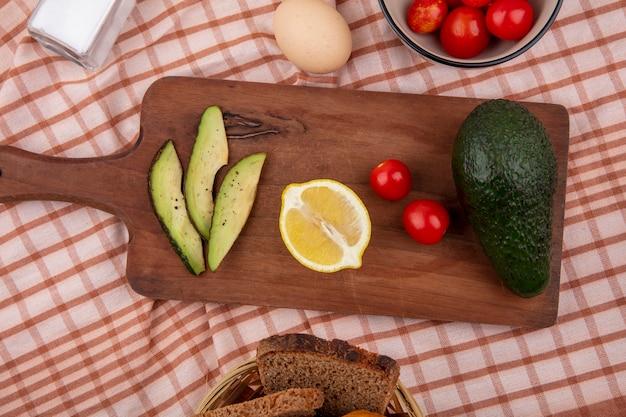 Вид сверху свежих ломтиков авокадо на деревянной кухонной доске с половинкой лимона и целыми помидорами авокадо на проверенной скатерти