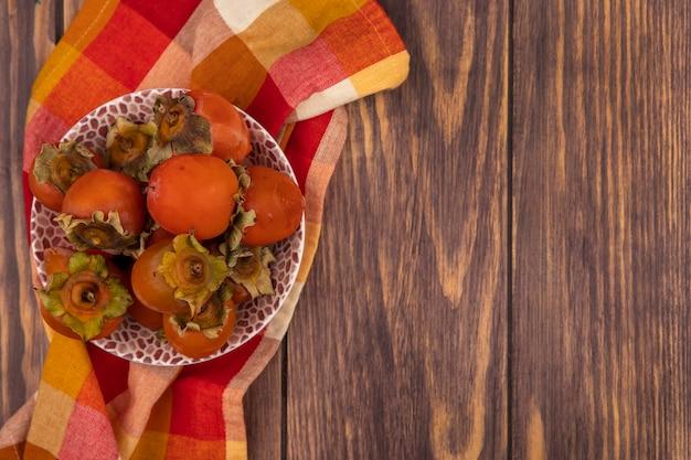 コピースペースと木製の背景にチェックの布の上のボウルに新鮮な柔らかくてジューシーな柿の上面図