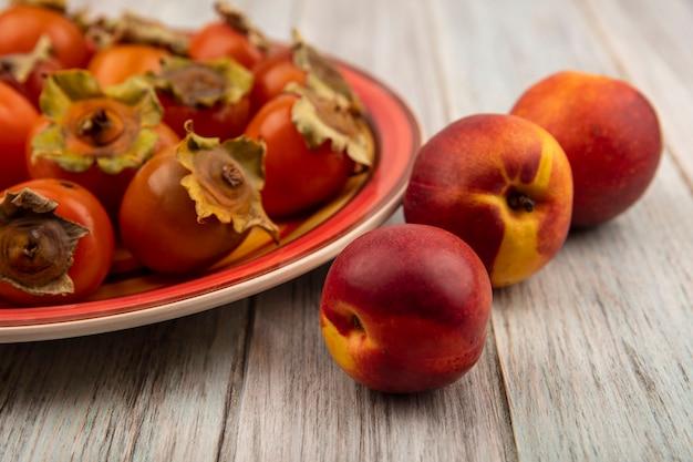 Вид сверху свежей мягкой и сочной хурмы на тарелке с персиками, изолированными на серой деревянной стене