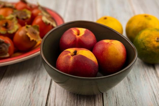 Вид сверху свежих мягких персиков на миске с мандаринами, изолированными на серой деревянной стене