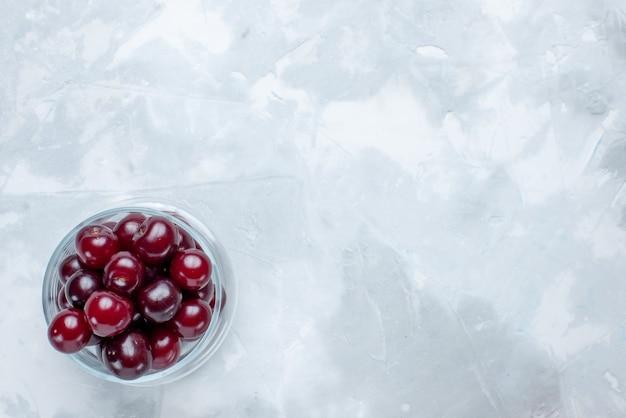明るい白い机の上の小さなガラスのカップの中の新鮮なサワーチェリー、フルーツサワーベリービタミンの上面図