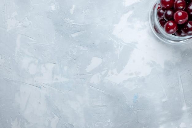 ライトホワイトフロアの小さなガラスカップの中の新鮮なサワーチェリーの上面図フルーツサワーベリービタミン写真