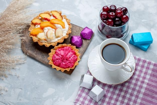 クリームケーキと白い光の机の上のお茶、フルーツサワービタミンスイートと小さなガラスカップ内の新鮮なサワーチェリーの上面図