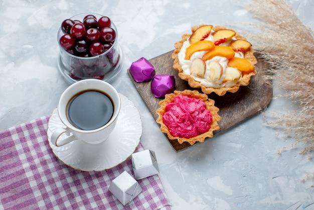 クリームケーキと白い光の上のお茶、フルーツサワーベリービタミンスイートと小さなガラスカップ内の新鮮なサワーチェリーの上面図