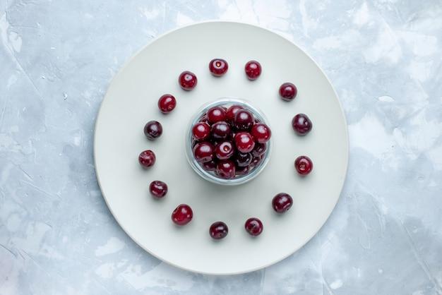 Вид сверху свежей вишни внутри тарелки на светлом столе, фруктовый кисло-ягодный витамин летом