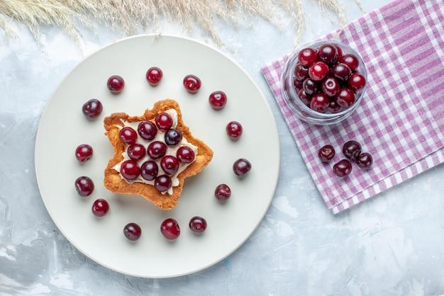 真っ白な机の上の星型のクリーミーなケーキ、フルーツサワーサマーケーキビスケットとプレート内の新鮮なサワーチェリーの上面図
