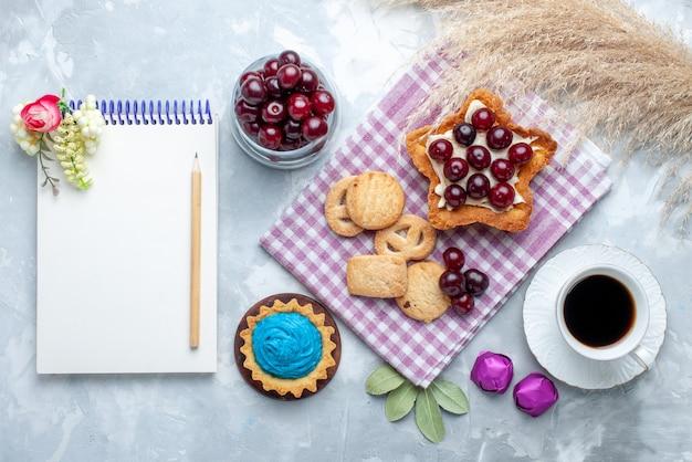 Вид сверху свежей вишни внутри тарелки с блокнотом для чая в форме звезды и кремового торта и печеньем на белом столе, фруктовый кислый торт