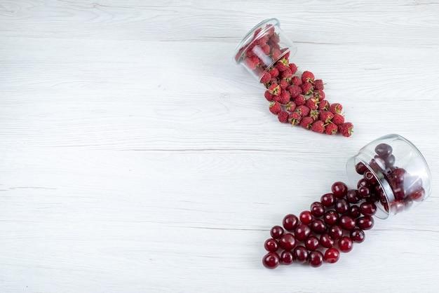 Вид сверху свежей вишни с малиной на свете, фруктово-ягодный мягкий сок