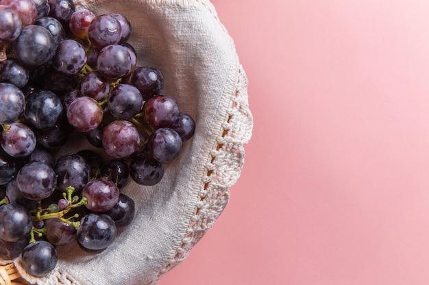 Вид сверху свежего кислого винограда внутри корзины на розовой поверхности