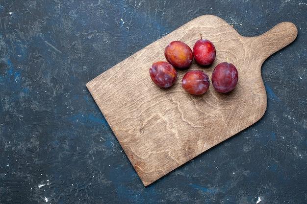 Вид сверху на свежие кислые сливы, цельные и сочные на темном столе, свежие ягоды