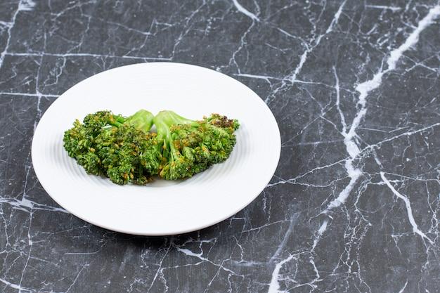 Вид сверху свежей вареной брокколи на белой тарелке.
