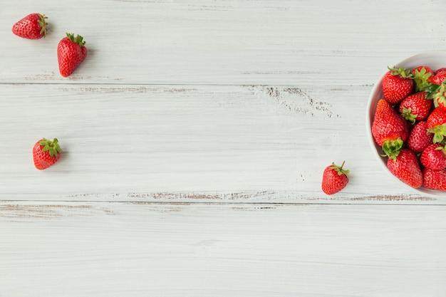 白い木製の背景の上のセラミックボウルに新鮮なイチゴの上面図。健康的な食事とダイエット食品の概念。