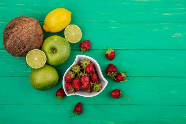 Вид сверху свежей клубники на миске с кокосовыми яблоками и лаймом на зеленом деревянном фоне с копией пространства