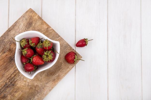 コピースペースを持つ白い木製の背景に木製キッチンボード上の白いボウルに新鮮なイチゴのトップビュー