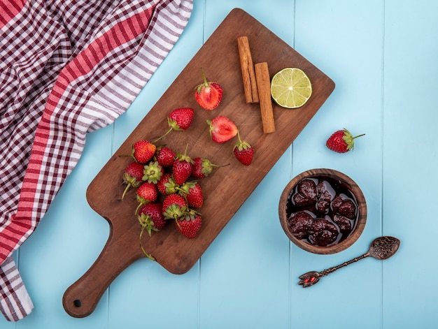 계피 나무 주방 보드에 신선한 딸기의 상위 뷰는 파란색 배경에 딸기 잼 스틱