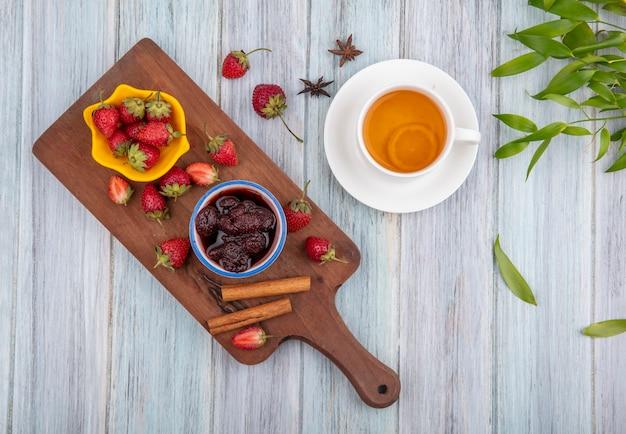 灰色の木製の背景の葉とお茶のカップとシナモンスティックといちごジャムの木製キッチンボード上の黄色のボウルに新鮮なイチゴの平面図