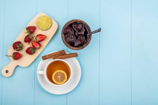 コピースペースと青色の背景に木製のボウルにいちごジャムと木製キッチンボードに新鮮なイチゴのトップビュー