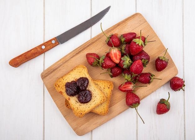 Вид сверху свежей клубники с поджаренным хлебом на деревянной кухонной доске с ножом на белом фоне