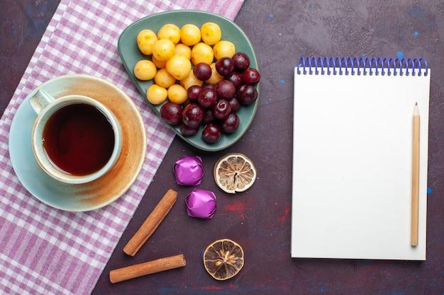 暗い表面にお茶とメモ帳のカップとプレート内の新鮮な甘いサクランボの上面図