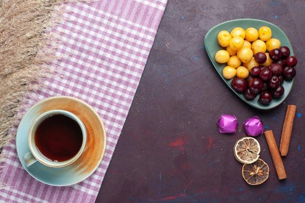 Вид сверху свежей черешни внутри тарелки с чаем и конфетами на темной поверхности