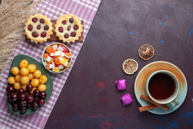 Вид сверху свежей черешни внутри тарелки с чайными пирожными и конфетами на темной поверхности