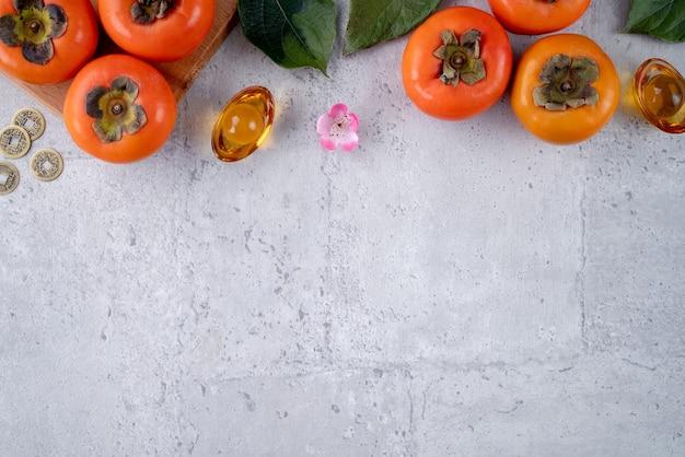 中国の旧正月の概念のための灰色のテーブルに葉を持つ新鮮な甘い柿柿の上面図、単語は春が来ることを意味します。
