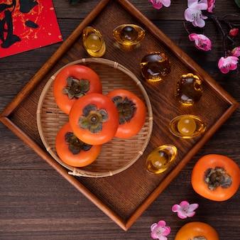 中国の旧正月の果物のデザインコンセプトの木製テーブルの背景に葉を持つ新鮮な甘い柿柿の上面図、この言葉は祝福が来ることを意味します。