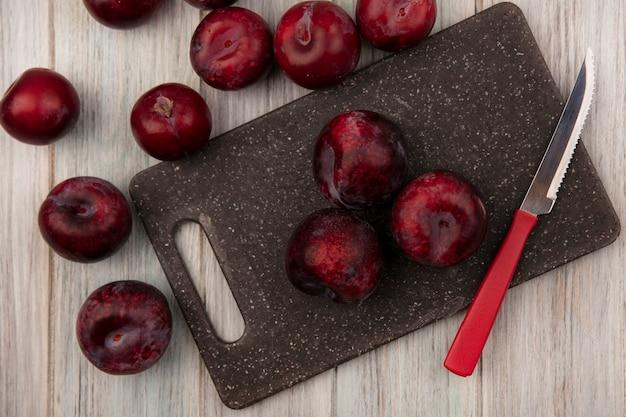 灰色の木製の壁にナイフで黒いキッチンボードに分離された新鮮な甘いプルオットの上面図