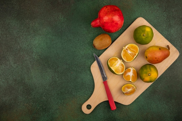 梨ザクロやコピースペースのキウイなどのおいしい果物とナイフで木製のキッチンボード上の新鮮なみかんの上面図