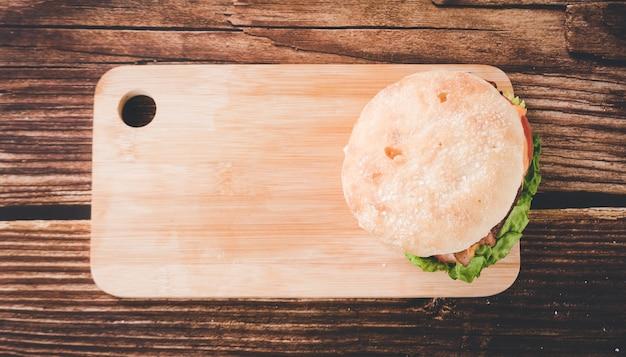 木製のテーブルの上の新鮮なおいしいハンバーガーの上面図。コピースペース