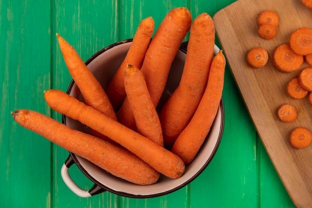Вид сверху свежей вкусной моркови на миске с нарезанными ломтиками на деревянной кухонной доске на зеленой деревянной стене