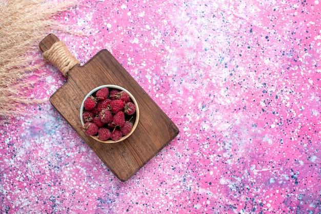 Вид сверху свежей вкусной малины внутри белой тарелки на розовой поверхности
