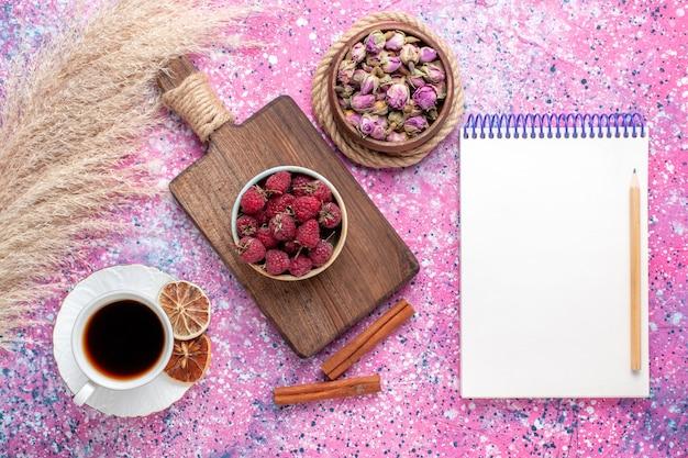 Вид сверху свежей вкусной малины внутри белой тарелки с чаем и корицей на розовой поверхности
