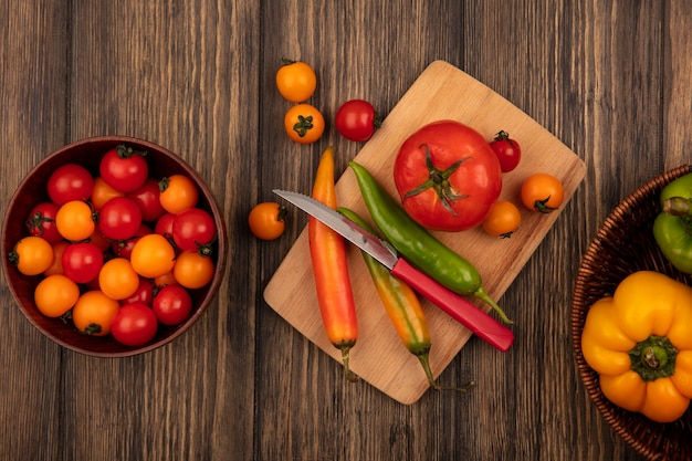 木製のキッチンボード上のフレッシュトマトの上面図とナイフ、木製のボウルにチェリートマト、木製の表面のバケツにピーマン
