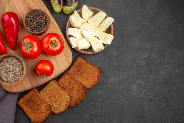 濃い色のフレッシュトマトの上面図。黒地にパンと白チーズ