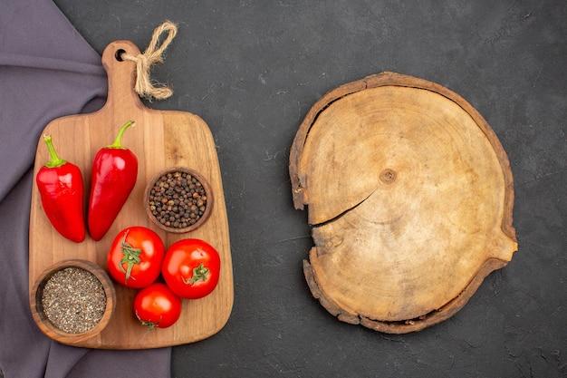 黒いテーブルに調味料とフレッシュトマトの上面図